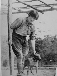 Edna Walling petting a dog.